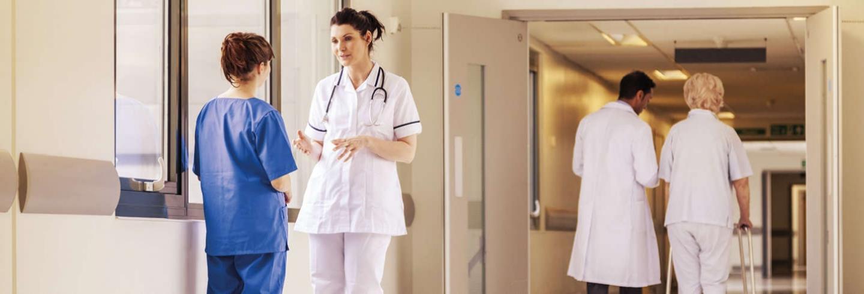 Verpleegkundigen met elkaar in gesprek in een ziekenhuis gang