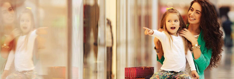 Moeder en kind winkelen in schone omgeving met veel glas