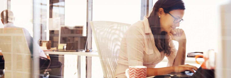 Vrouw geconcentreerd aan het werk in kantoorgebouw
