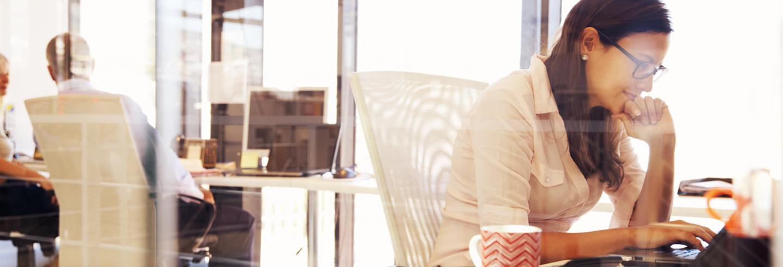 Foto van vrouw met bril in overhemd die op haar laptop werkt op kantoor