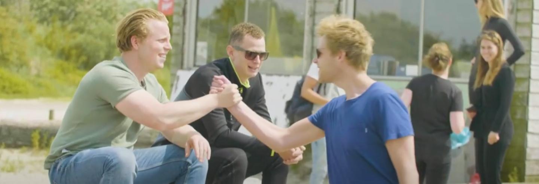 Twee leden van Jong Facilicom geven elkaar een hand tijdens een Jong facilicom bijeenkomst in de buitenlucht.