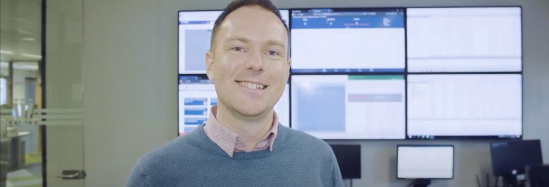 Collega bij Breijer poseert voor de camera en staat voor zes tv-schermen.