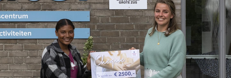 Diede Smit overhandigt een cheque ter waarde van 2500 euro aan een vrijwilligster van Stichting Grote Broer