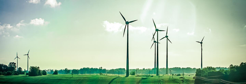 Groen en zonnig landschap met mooie blauwe lucht met paar schapenwolkjes en een aantal windmolens