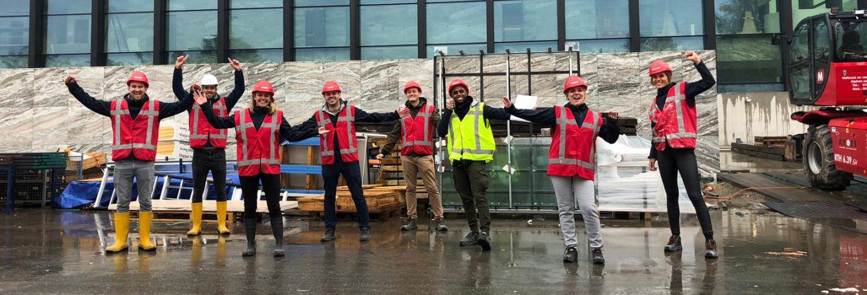 Een groepsfoto van de Facilicom Group trainees op een bouwplaats oranje hesjes aan en een bouwhelm op.