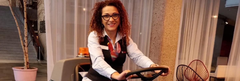Gabriela Smit die vrolijk rondrijdt op een schoonmaakmachine